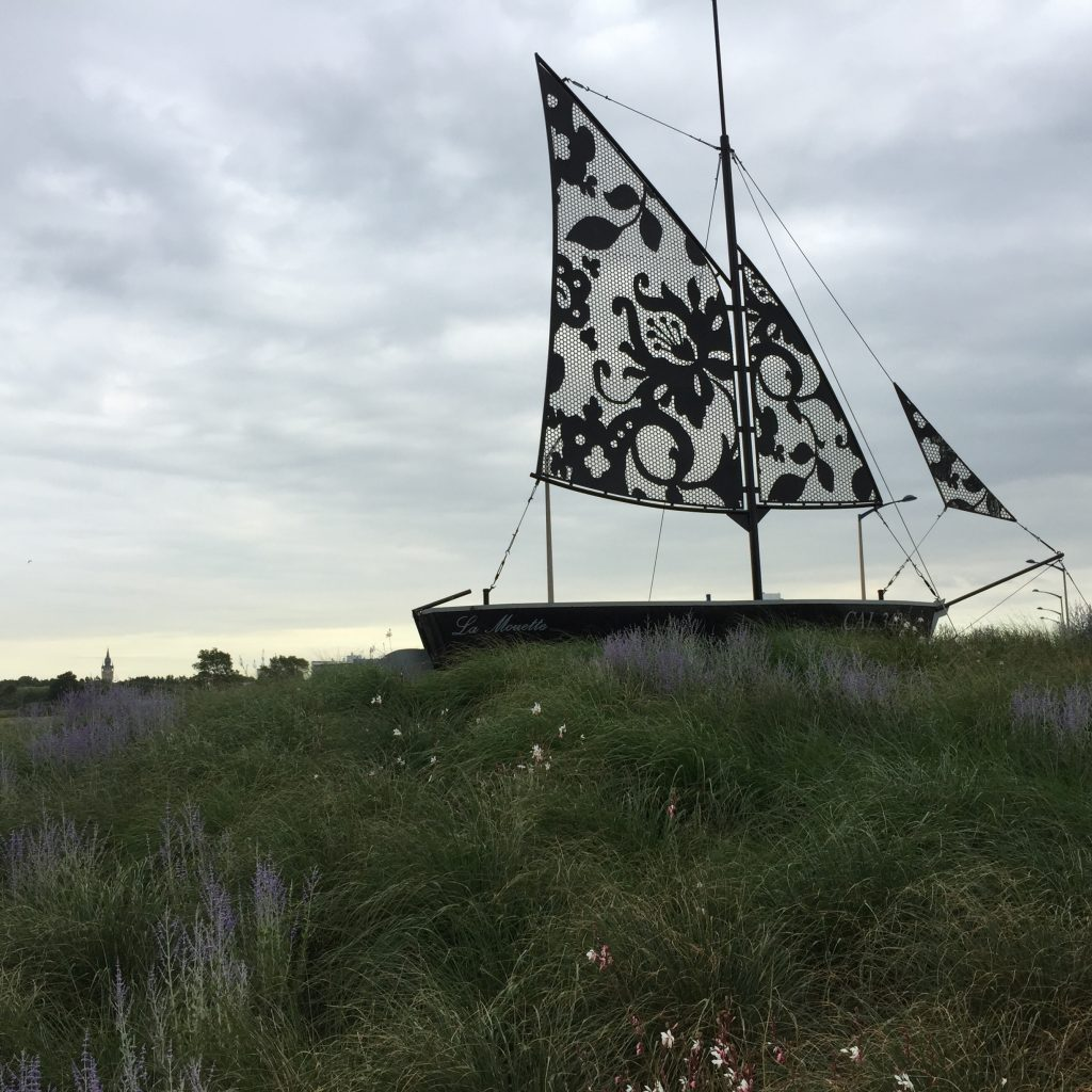 The Boat of Calais, La Mouette, The Seagull, with lace sail signaling renowned lace trade employing migrant labor, 2017